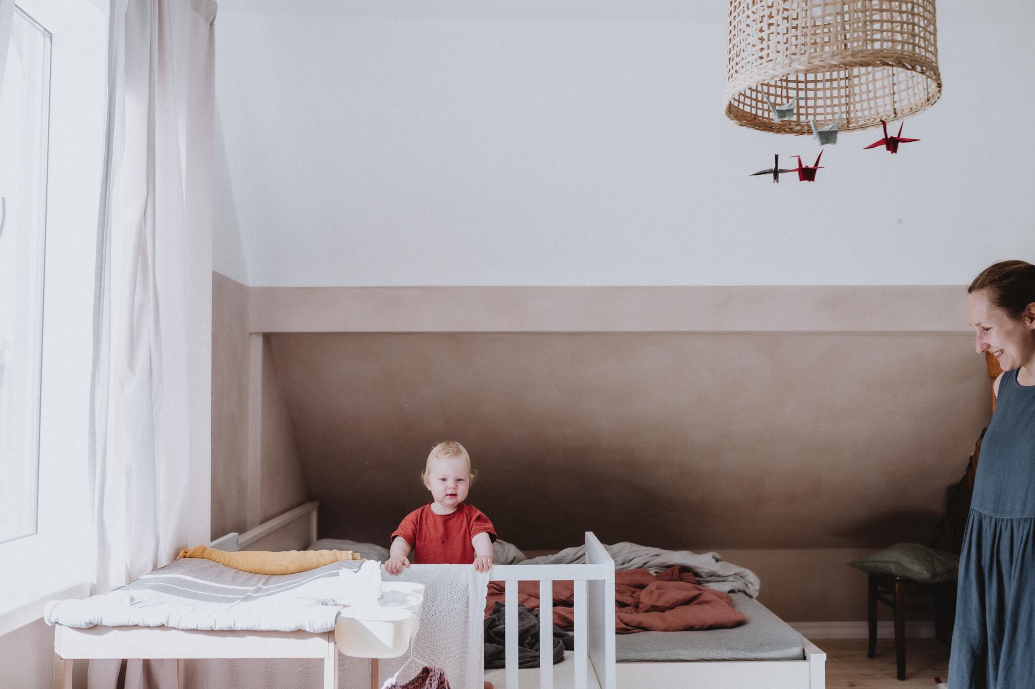 Kodune perepildistamine, laps ärkab hommikul oma toas, päike paistab ja ema vaatab teda.