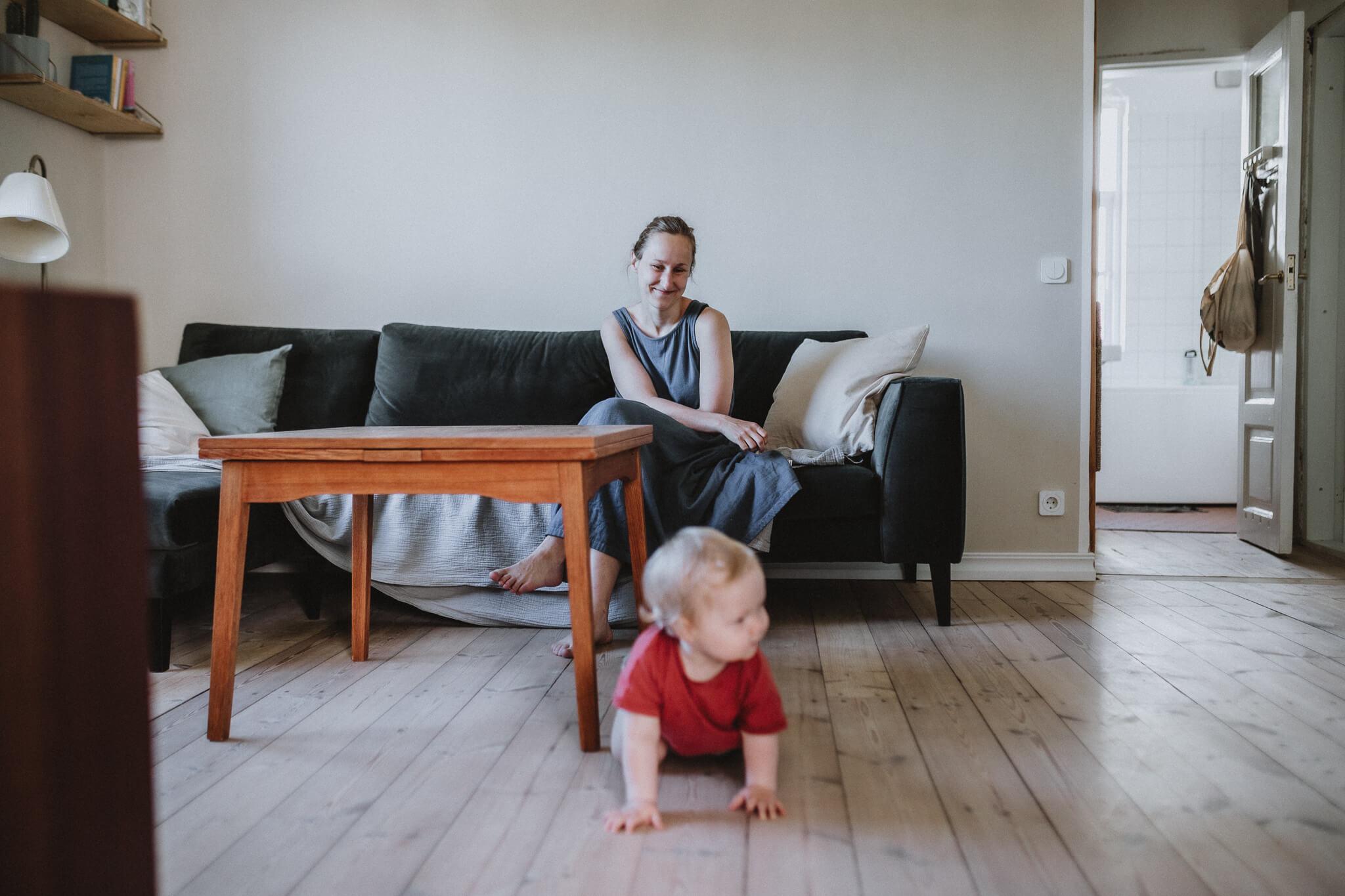 Kodune perepildistamine, ema diivanil ja laps roomab.