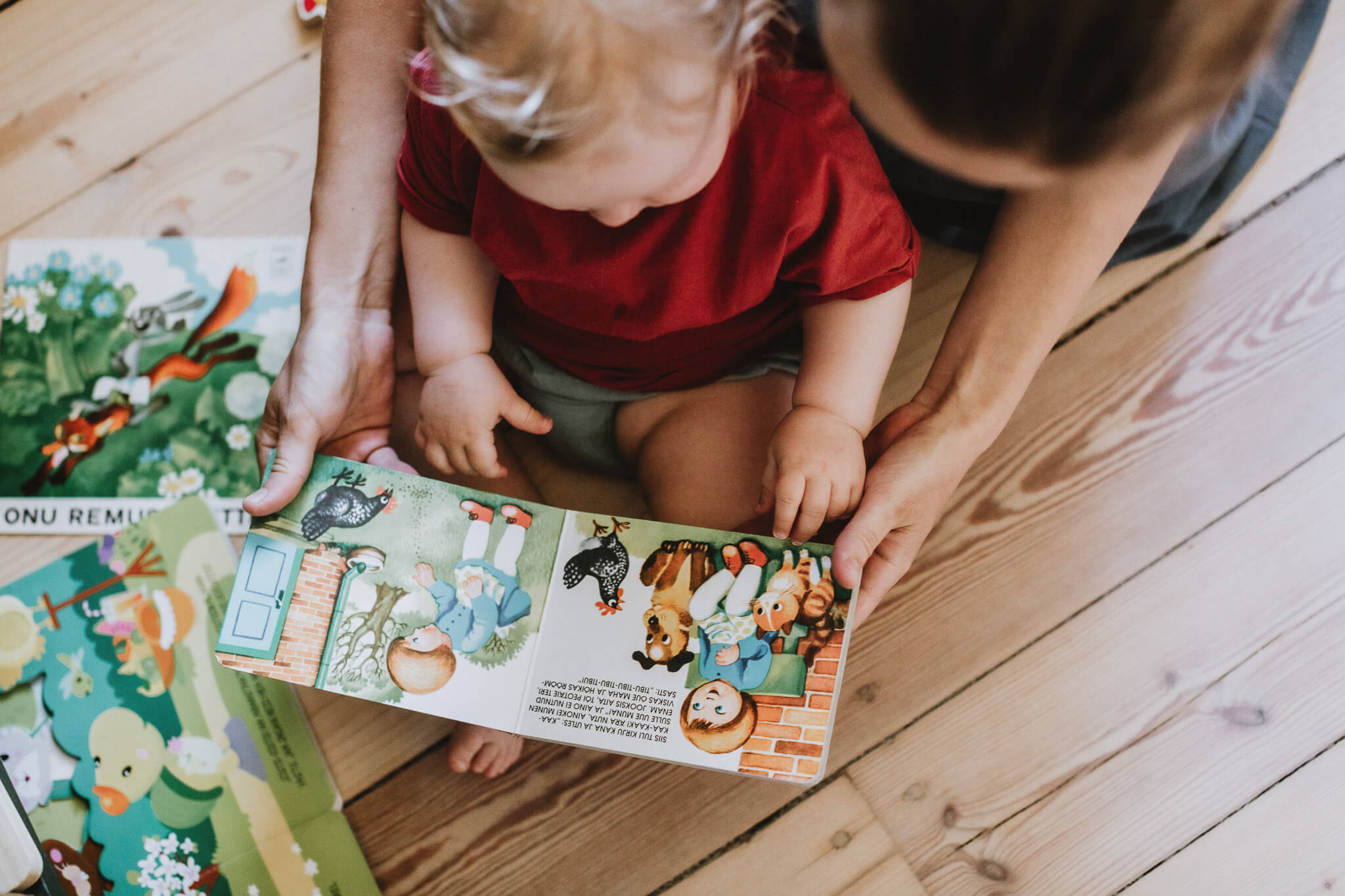 Dokumentalistlik foto emast, kes vaatab beebiga kõvade kaantega raamatut Muna.