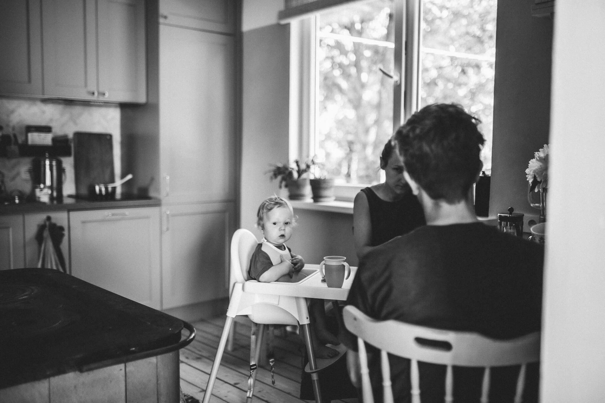 Doumentalistlik perepilt köögist, ema, isa ja beebi söövad putru, fookuses on laps söögitoolis.