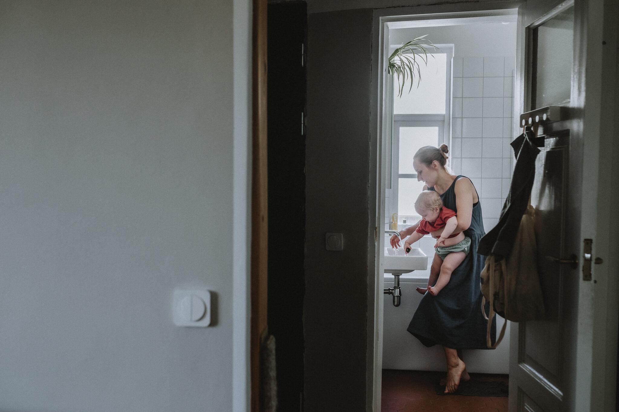 Dokuemtalistlik perepilt vannitoast, kus ema peseb beebil käsi kraanikausi ääres.
