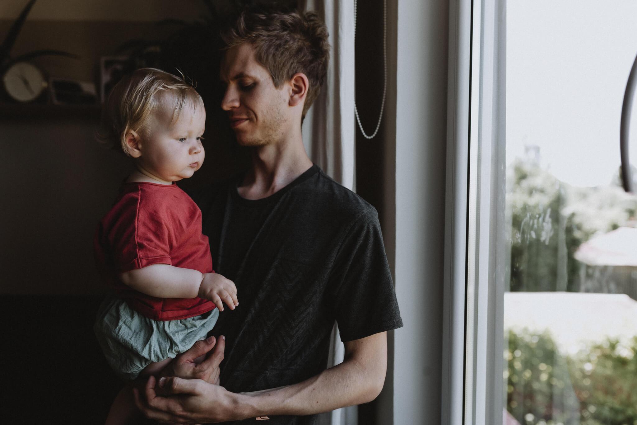 Portreefoto isast ja tütrest, sesiavad akna juures. Vaade Tammelinna, aps vaatab aknast välja.