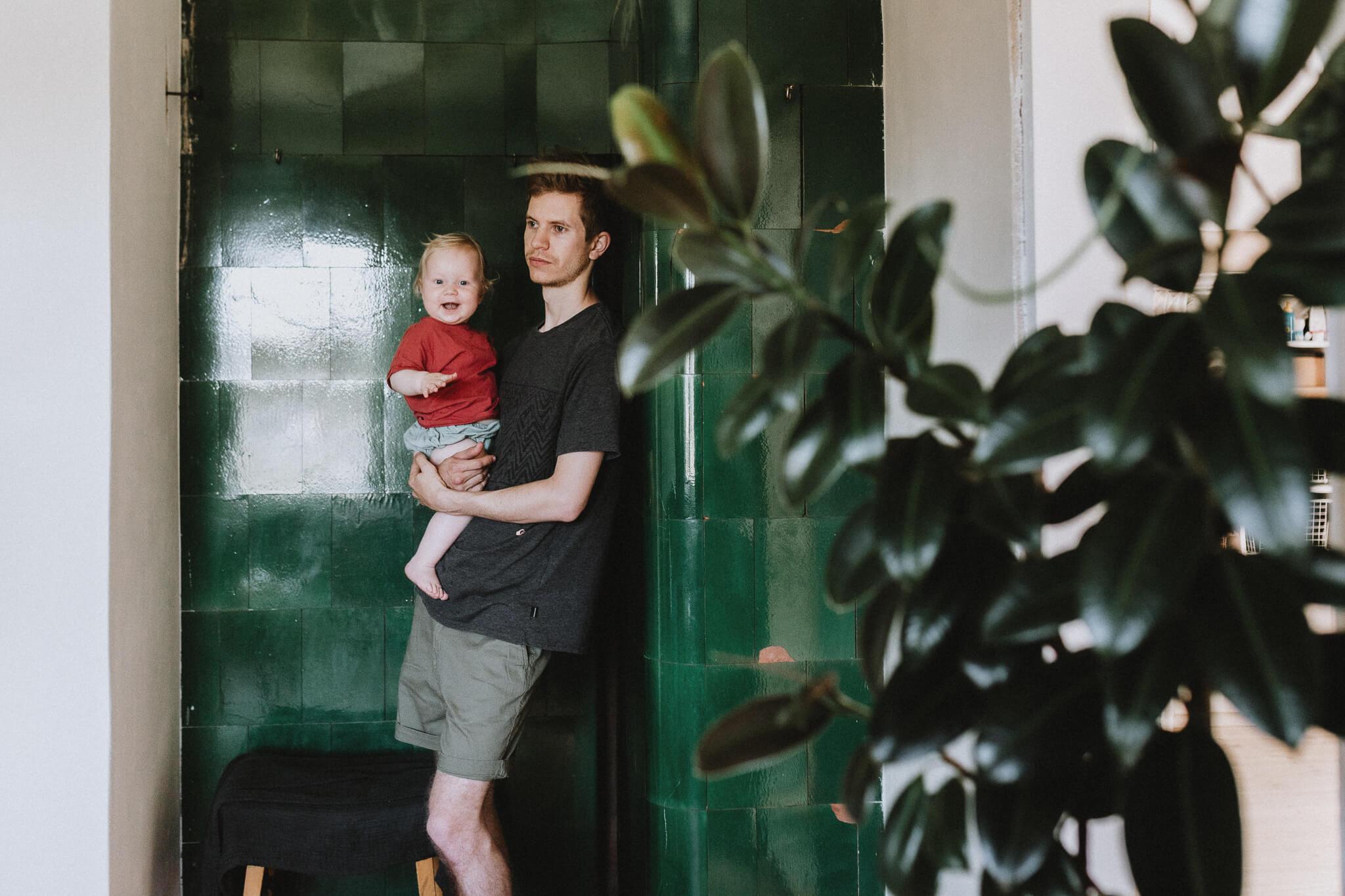 Portree isast ja tütrest, kes seisavad ahju ees. Laps naerab rõõmsalt.