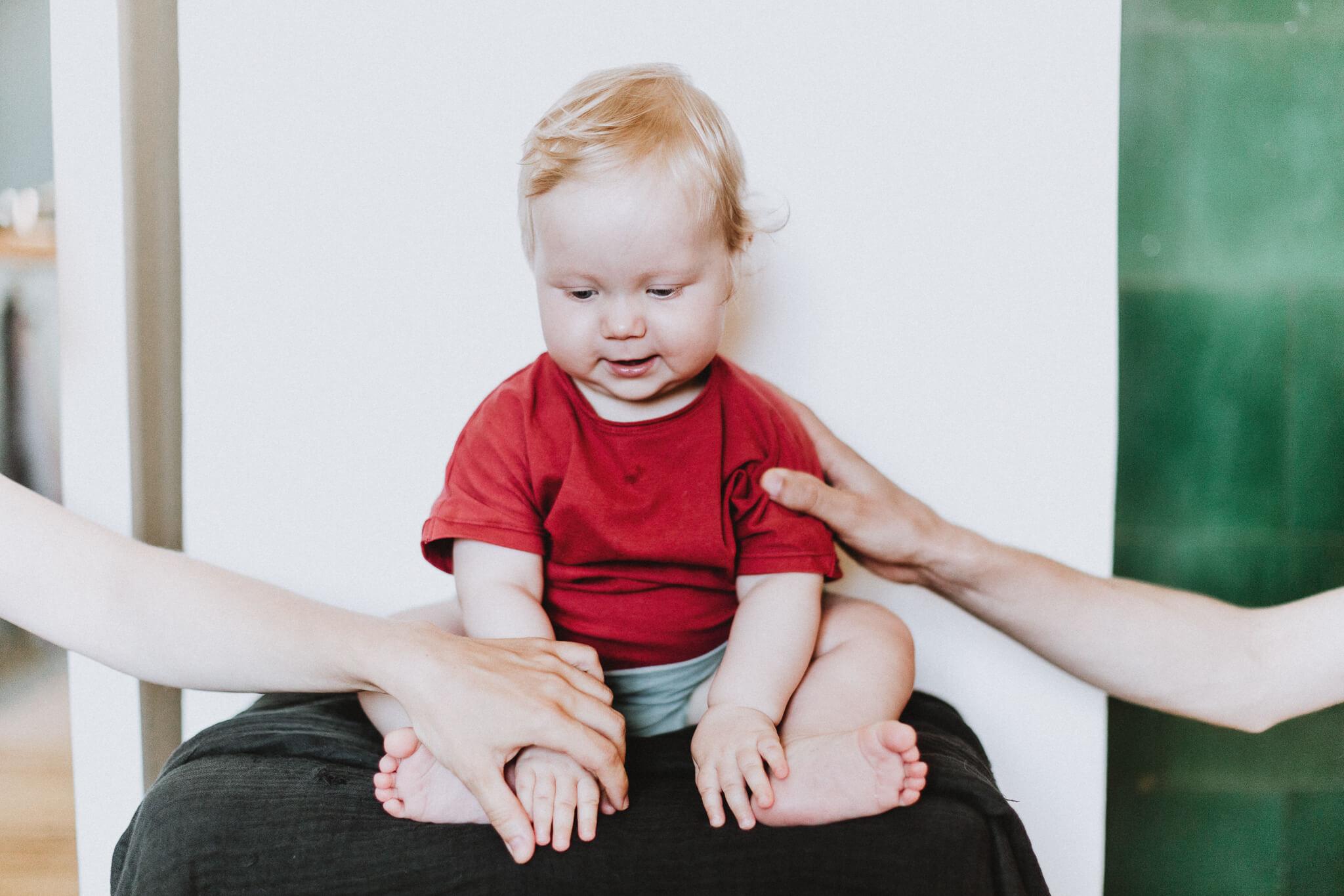 Portreefoto aastasest lapsest, kes istub taburetil ja keda ema ja isa toetavad kõrvalt.