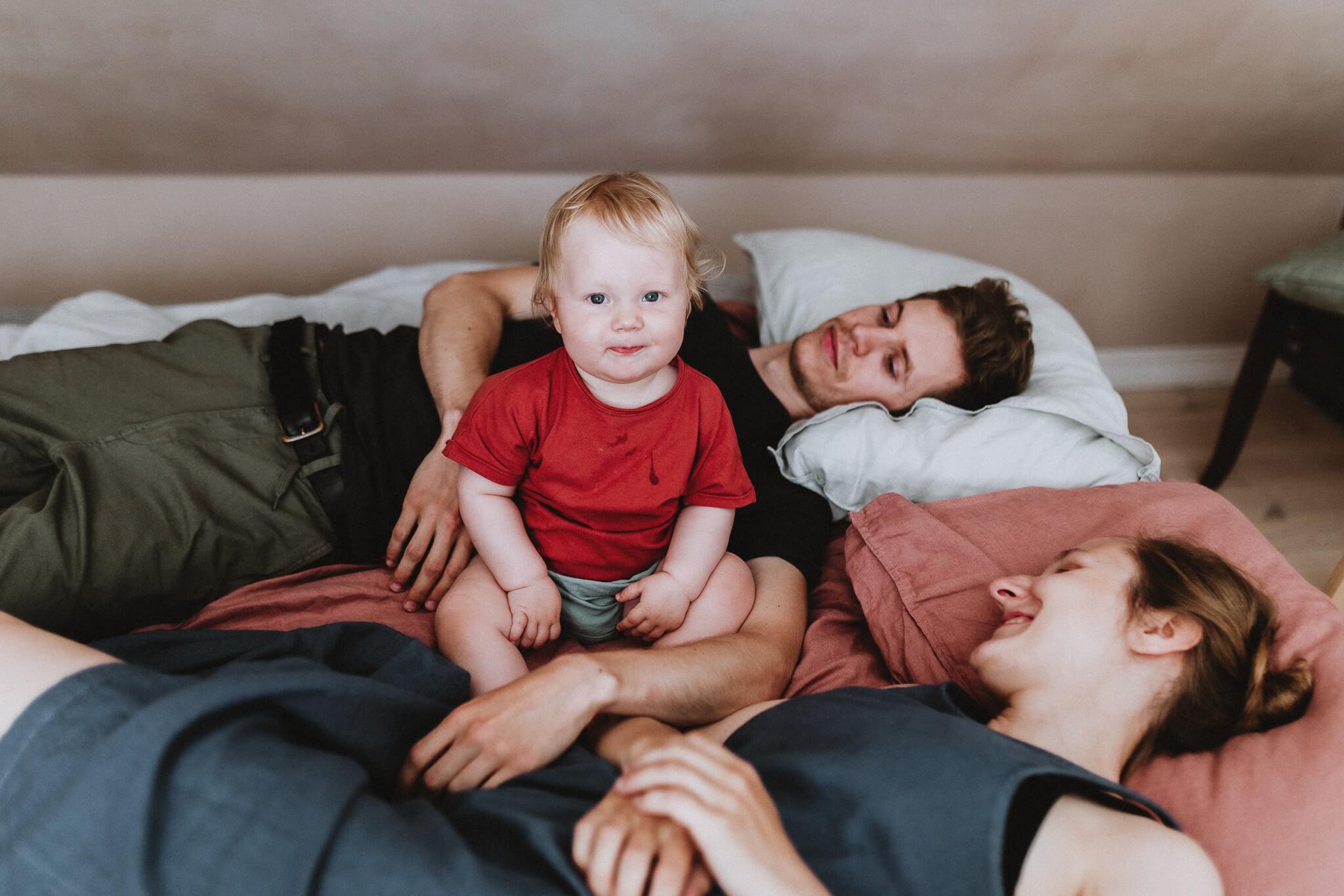 Portreefoto aastasest lapsest, kes istub voodi peal ema ja isa vahel.