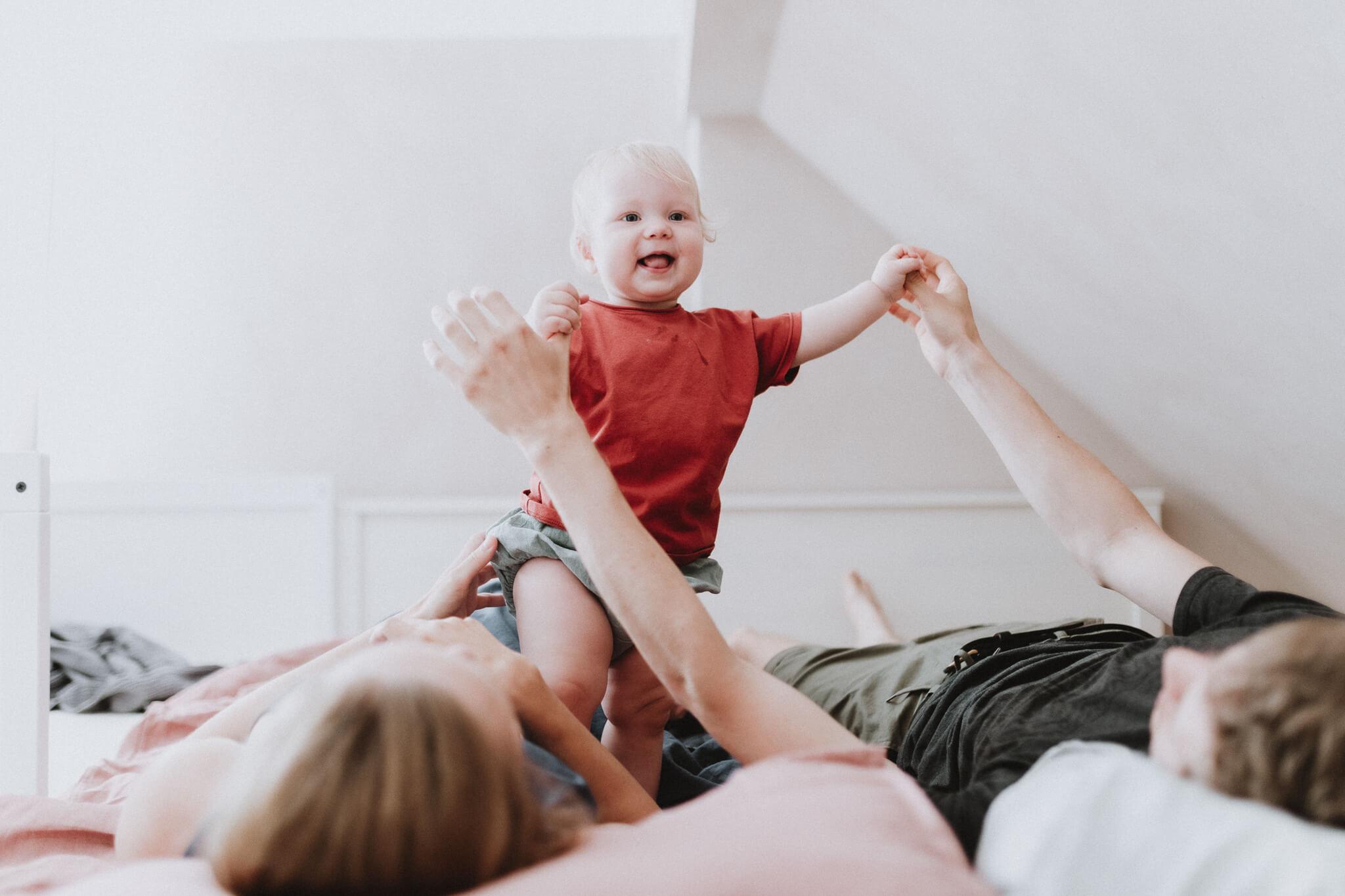 Portreefoto aastasest tüdrukust, kes seisab voodi peal ja hoiab isa kätest kinni.