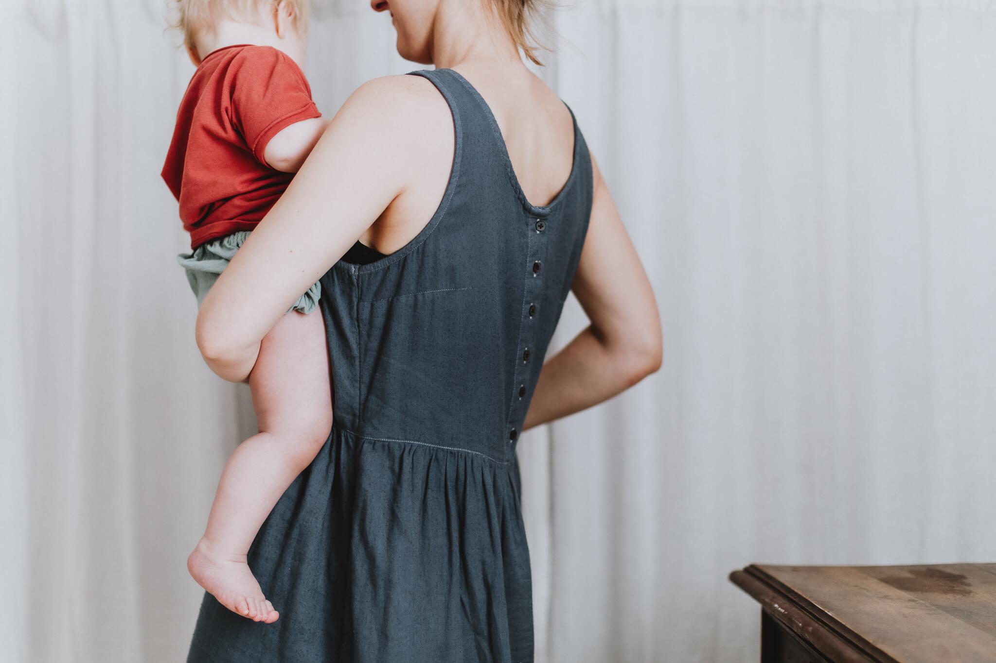 Detailsem foto emast, kes hoiab last oma süles.