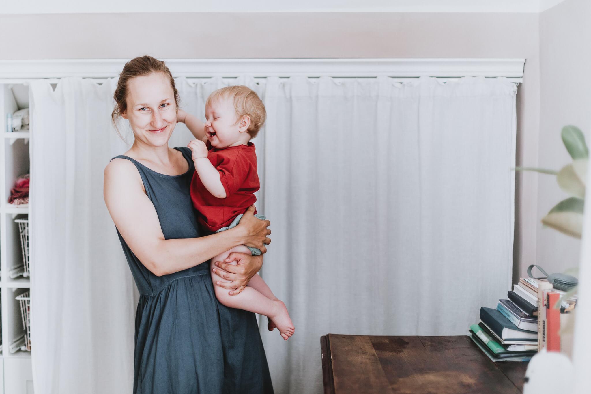 Lõbus foto emast, kes hoiab oma pisikest tütart süles ja mõlemad naeravad.