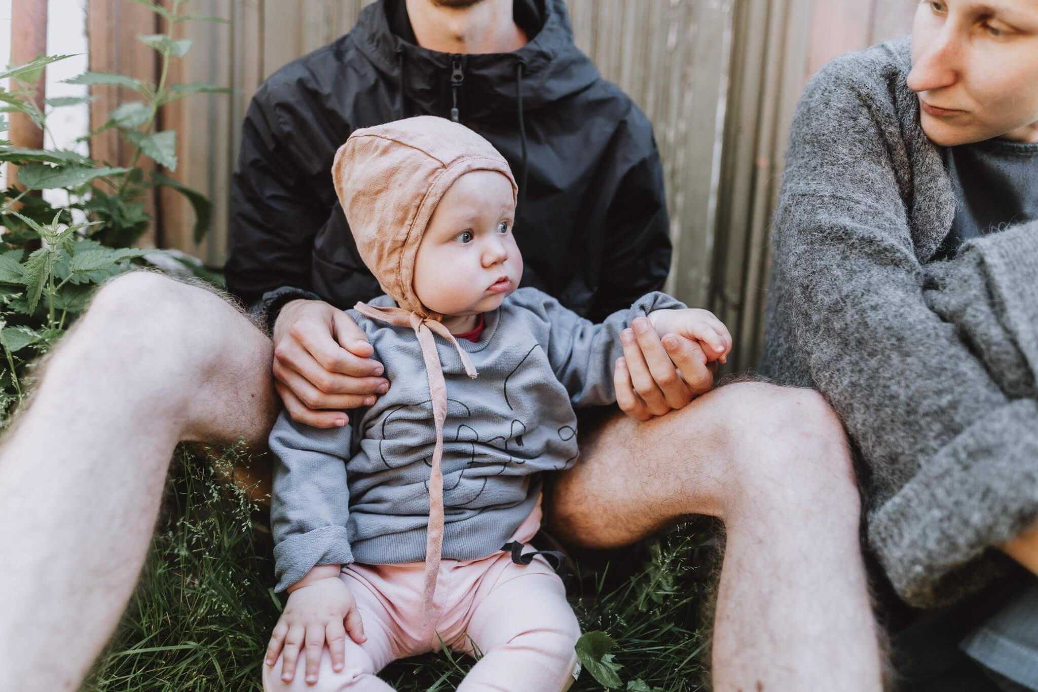 Portreefoto mütsiga beebist, kes istub õues isa süles, ema on kõrval.