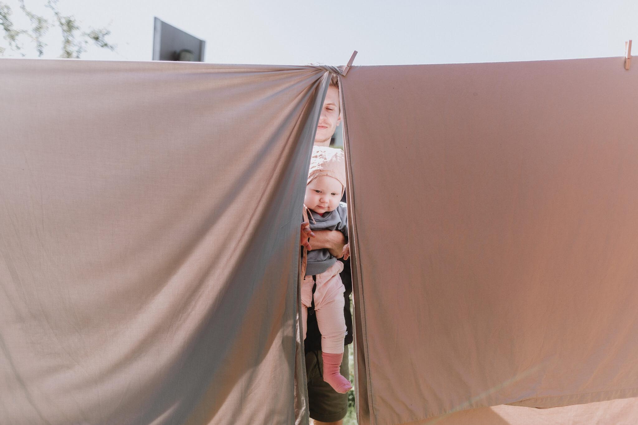 beebi on isa süles ja mõlemad piiluvad läbi linade, mis ripuvad õues pesunööril.