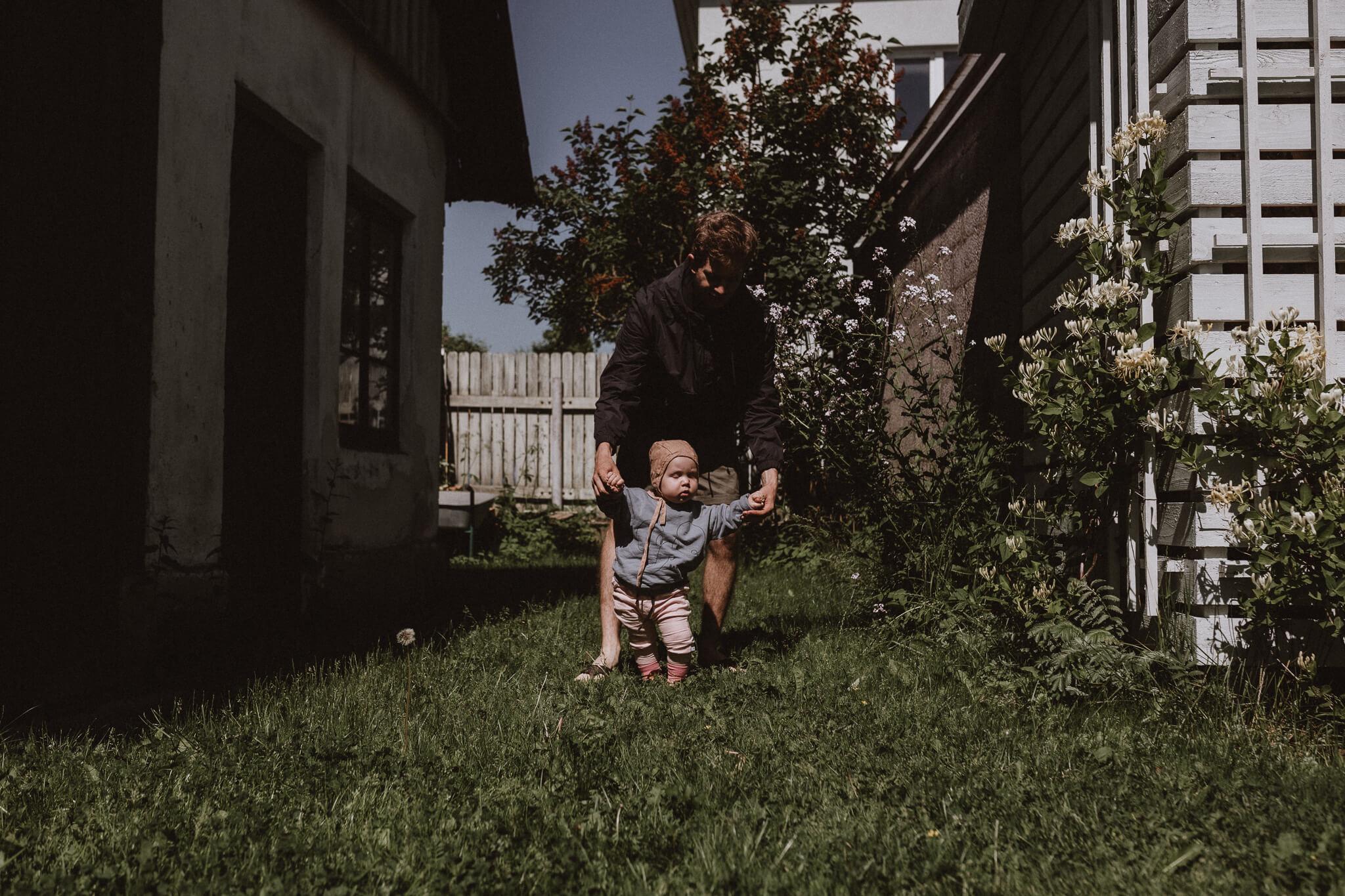 Aastane laps kõnnib isa käekõrval Tartus Tammelinna aias.