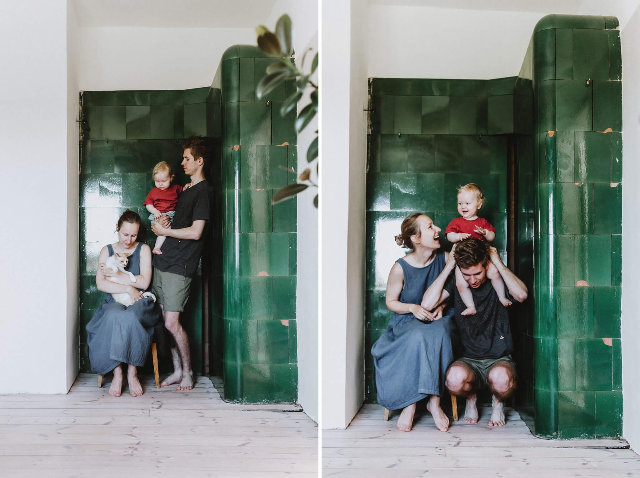Kaks elustiilifotot perest, kes on ahju ääres - ema istul kassiga ja isa seisab tütrega kõrval.