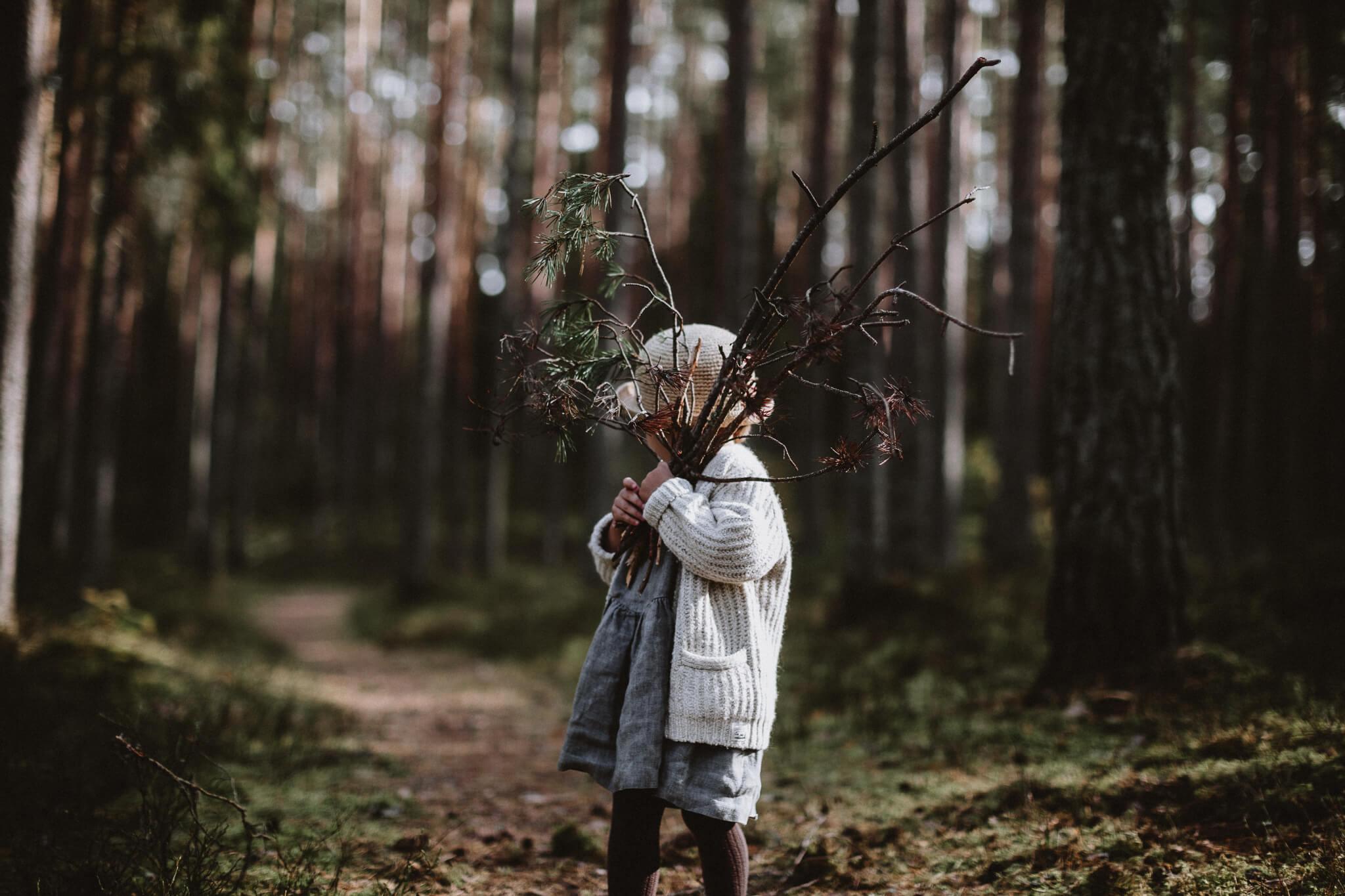 Portreefoto väikesest tüdrukust metsas, kes hoiab käes suurt oksakimpu