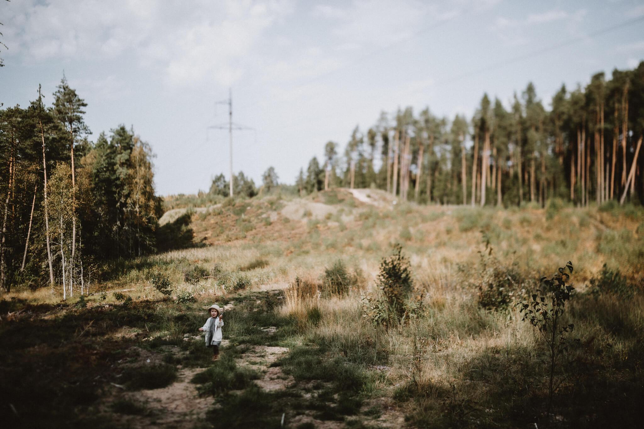 Väike tüdruk jalutab metsalagendikul