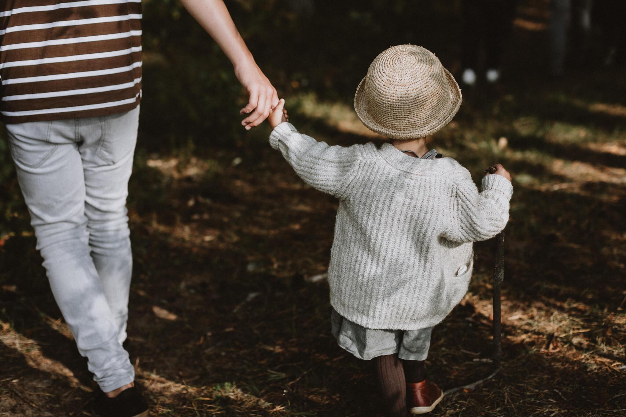 Väike tüdruk jalutab metsas käest kinni koos suurema poisiga