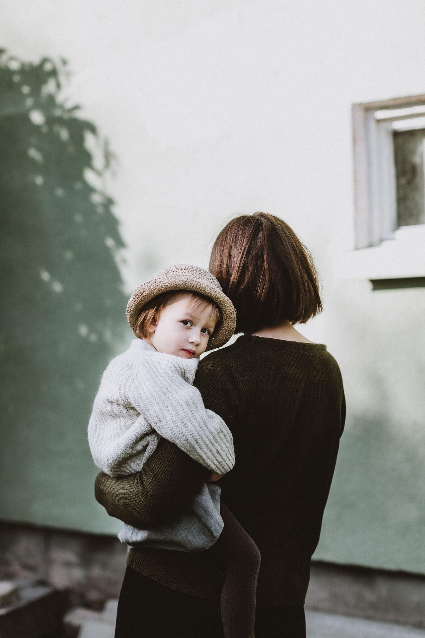 Portreefoto tüdrukust, kes on ema süles ja vaatab üle õla.