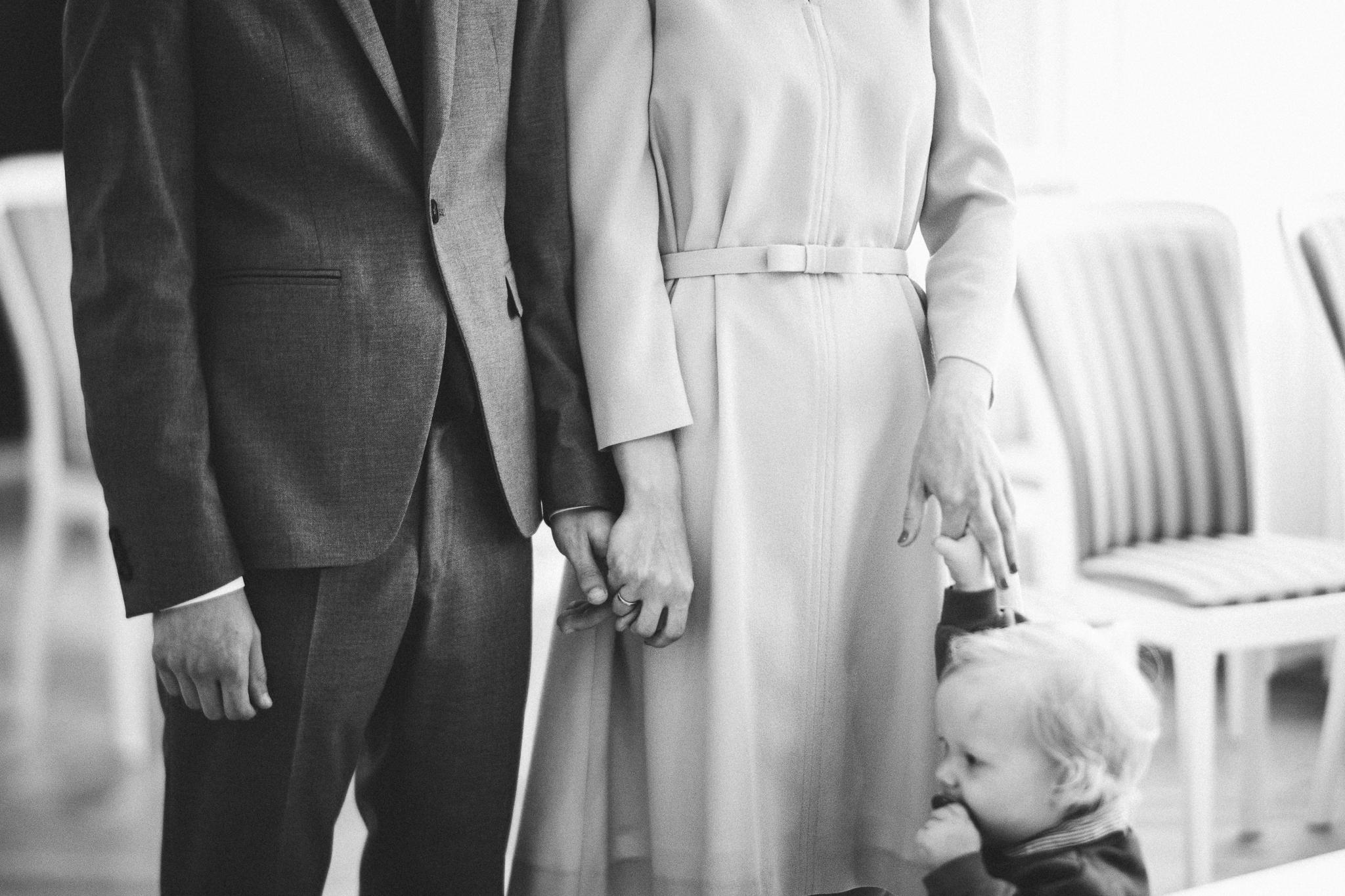 Mustvalge pilt laulatusest, pruut peigmees ja väike laps.